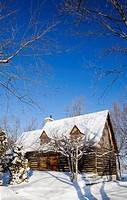 Old reconstructed Canadiana cottage_style residential log home, 1975, in winter, Quebec, Canada. This image is property released for book, calendar, m...