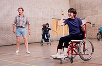Young girl with disability, who is wheelchair user, taking part in ball game in sports hall,