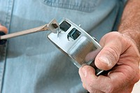 An electrician using a screwdriver to remove the knock_outs tabs from an electrical box. Work is being performed according to code by a licensed maste...