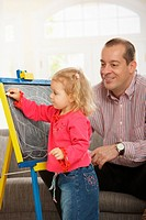 Smiling dad watching small daughter drawing on board at home.