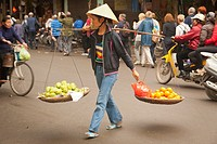 Woman walking across a road carrying fruit in the old town, Hanoi, Vietnam