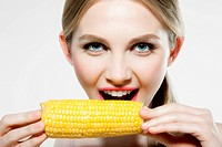 Young woman biting corn cob