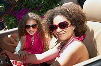 A pair ofmixed race young girls wearing sunglasses sitting inside a car
