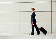 Businesswoman walking pulling luggage