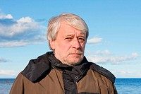 Portrait of mature concerned man with grey hair at the Baltic sea in autumn day.
