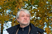 Portrait of mature serious man with grey hair in autumn day.