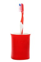 Toothbrush in a red glass on a white background
