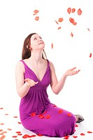 Beautiful redhead girl in purple dress showered by red rose petals