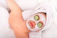 Young lady with facial mask and cucumber on eyes