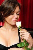 Beautiful young woman picking up the scent of a rose, with an introvert smile on her face