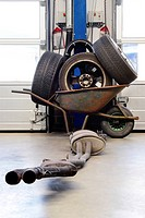 Wheelbarrow with various wheels and an exhaust,silencer system and tires in front of two garage doors in a mechanics workshop