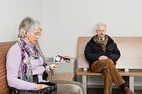 Elderly woman, sitting on a bench in the waiting room of a hospital with a portable music player in her hands