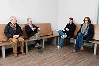Four people waiting for their turn in the sparse waiting room of a hospital clinic