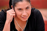 Young mixed raced woman in black sportswear, listening to music with headphones