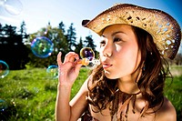 A beautiful asian girl having fun playing bubbles outdoor during summer