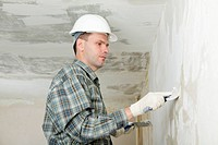 Contractor in white hardhat plastering a wall