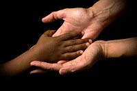 White woman´s hands receive the black child´s hand