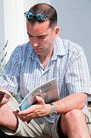 Man with hearing impairment studying book