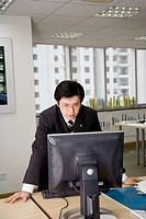Businessman Standing at Computer