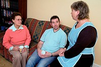 Carer talking older woman and her son at home