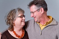Portrait of a middle aged couple smiling at one another