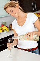 Woman In Kitchen Pouring Glass Of White Wine
