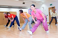 Group of adults taking part in aerobics class at leisure sports centre,
