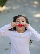 Young girl licks a cherry popsicle.