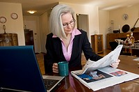 Businesswoman Reading Newspaper at Home