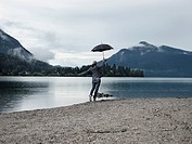 Woman carrying umbrella by still lake