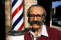Barber with Mustache Standing Next to a Barber Pole