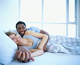 Couple Smiling and Relaxing in Bed