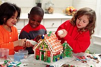 Friends preparing a gingerbread house