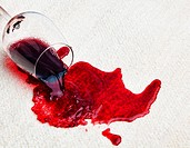 Ein Glas mit Rotwein wurde auf einem Teppich verschüttet. Schaden für Versicherung.