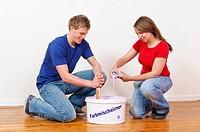 Ein junges attraktives Paar beim renovieren und streichen der ersten gemeinsamen Wohnung.
