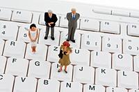 Mehrere Figuren und Geschäftsleute stehen auf einer Computertastatur