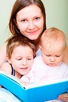 Familie beim Lesen im Bett