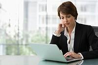 Caucasian businesswoman typing on laptop
