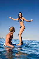 Man Helping Woman Stand on Surfboard