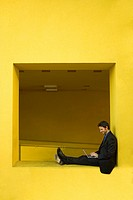 Businessman Using Laptop While on Yellow Wall