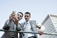 Young businessman checking his mobile phone and showing something to a colleague