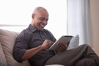 Black man sitting on sofa using digital tablet