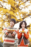 Young Couple Holding Maple Leaf In Hand