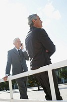 Businessmen leaning on railing
