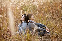Young Couple Sitting In Field