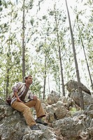 Man Sitting on Boulder