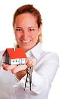 Immobilienmaklerin überreicht Hausschlüssel mit Miniaturhaus