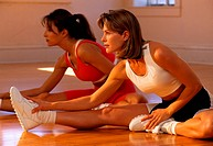 Two Women Stretching Arms to Toes