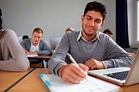 Student am Laptop macht Notizen im Unterricht