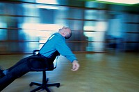 Businessman Rolling in Chair with Arms Spread